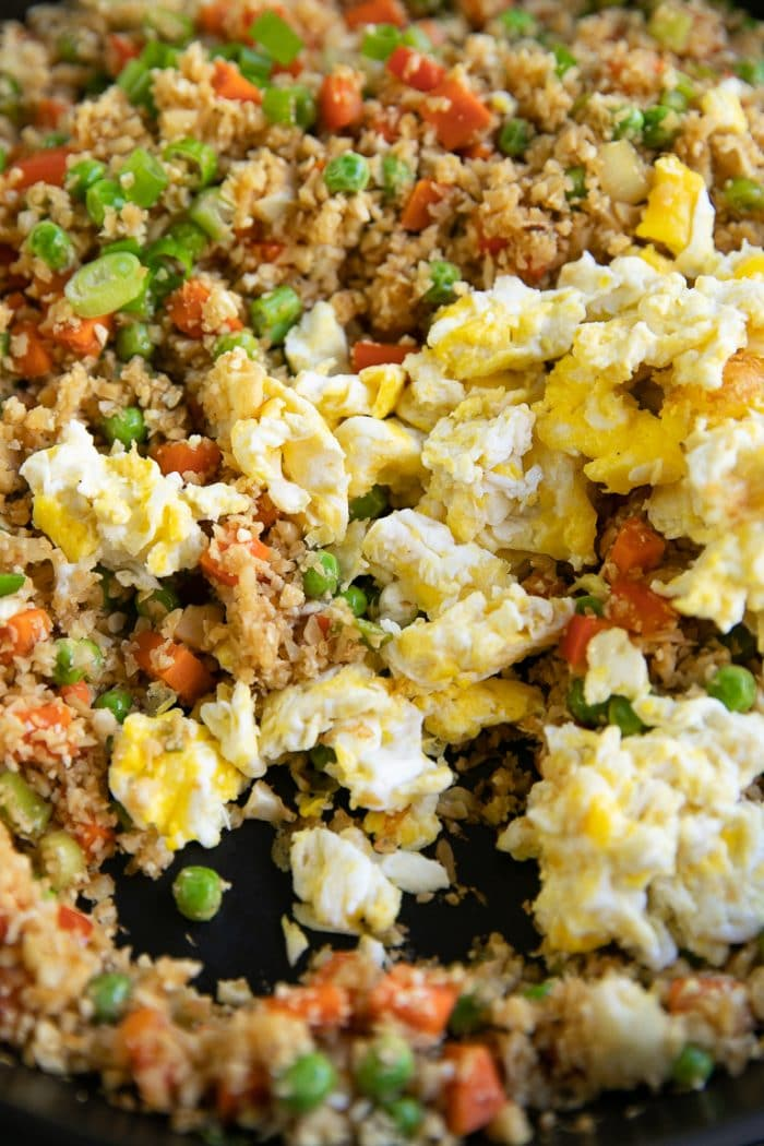 Scrambled eggs being added to cooked cauliflower fried rice.