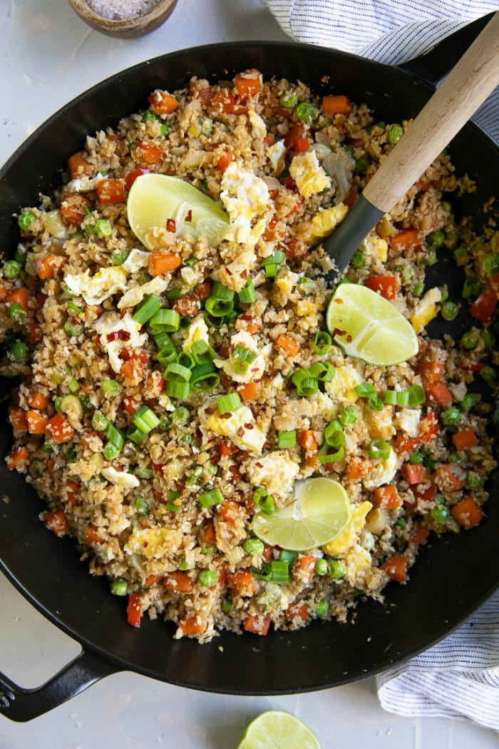 skillet filled with cooked cauliflower fried rice and garnished with lime wedges and chopped green onions.