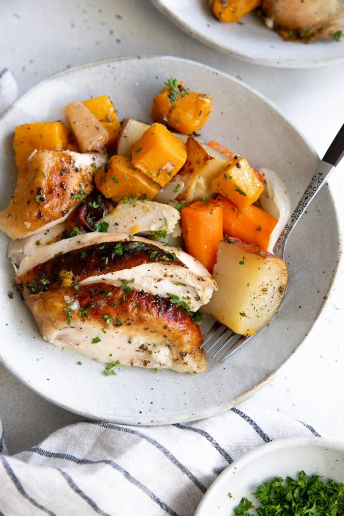 Plate filled with sliced roast chicken breast served with tender roasted vegetables.