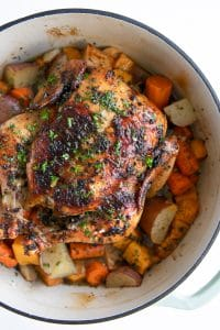 Roast chicken in a large round Dutch oven set atop a bed of vegetables.