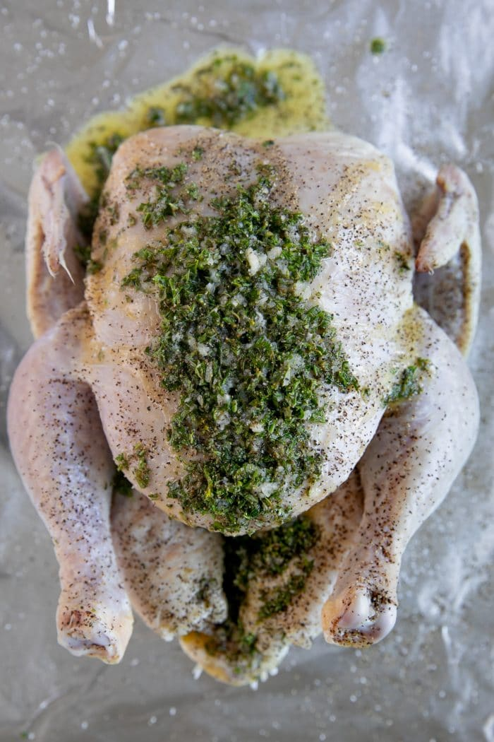 Raw chicken on a large baking sheet covered seasoned with salt and pepper and covered with butter, garlic, and fresh minced herbs.