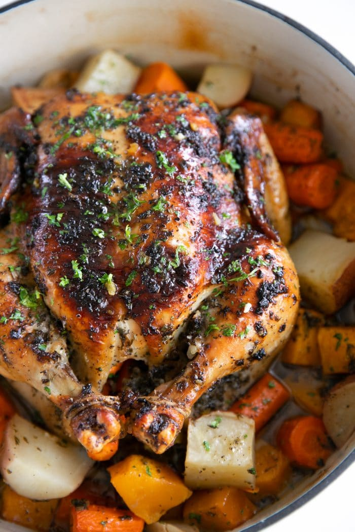 Perfect Roast chicken in a large round Dutch oven set atop a bed of vegetables.