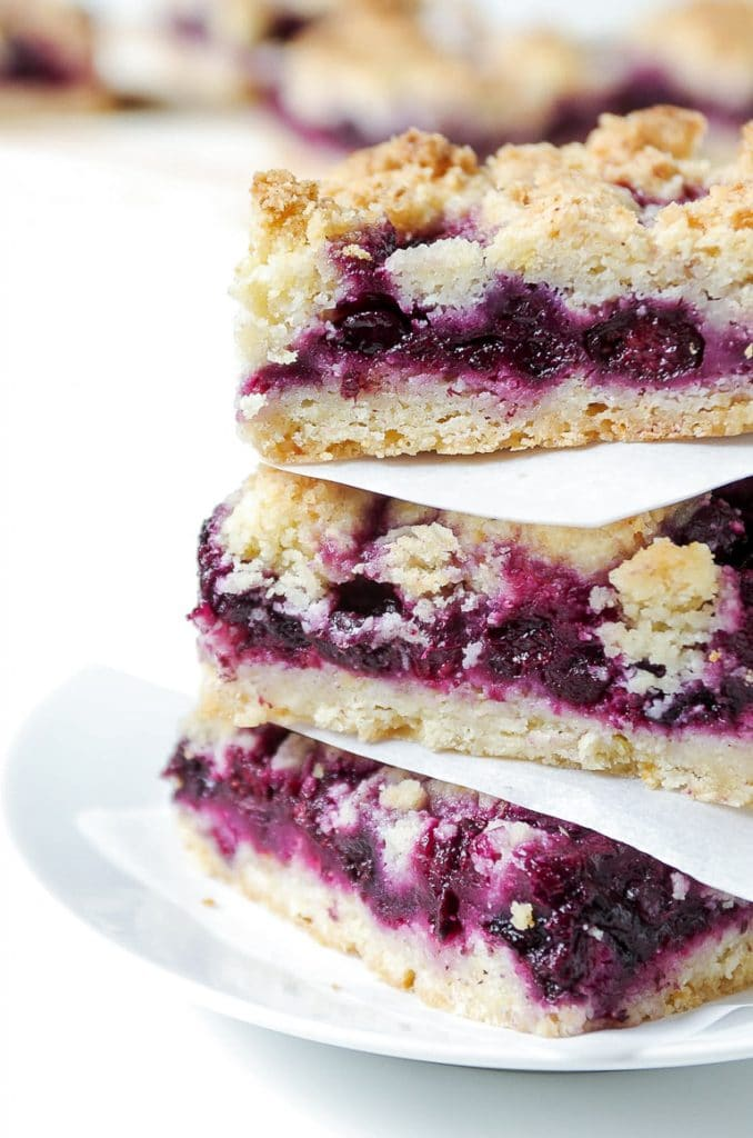 Three stacked Blueberry Crumb Bars on a white plate