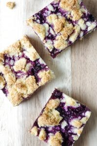 A piece of blueberry crumble bar sitting on top of a wooden cutting board
