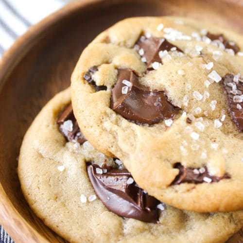 Small wooden plate holding two chocolate chunk cookies topped with flakey sea salt.