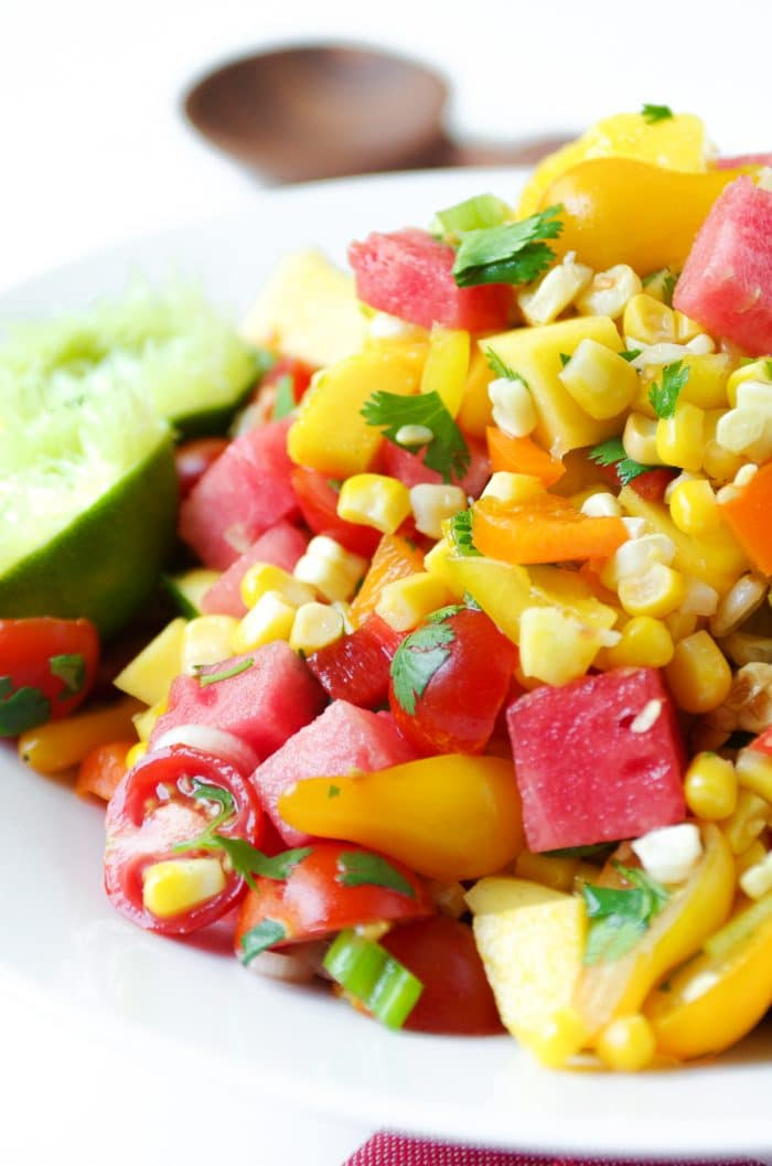 Large white bowl filled with a chopped salad made with grilled corn, watermelon and mango cubes, cherry tomatoes, cilantro, and fresh lime juice.
