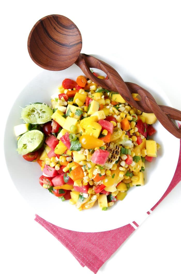 Large white bowl filled with a chopped salad made with grilled corn, watermelon, mango, cherry tomatoes, cilantro, and fresh lime juice.