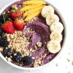 Acai bowl topped with fresh fruit and granola.
