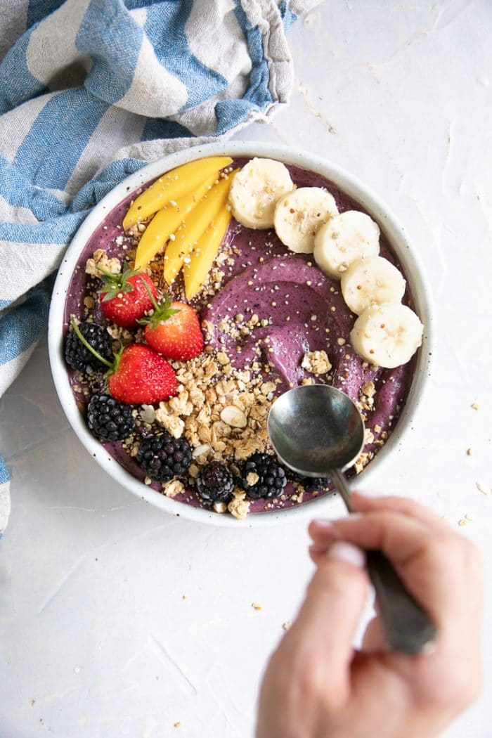 Hand holding a spoon about to take a scoop from a prepared acai bowl.