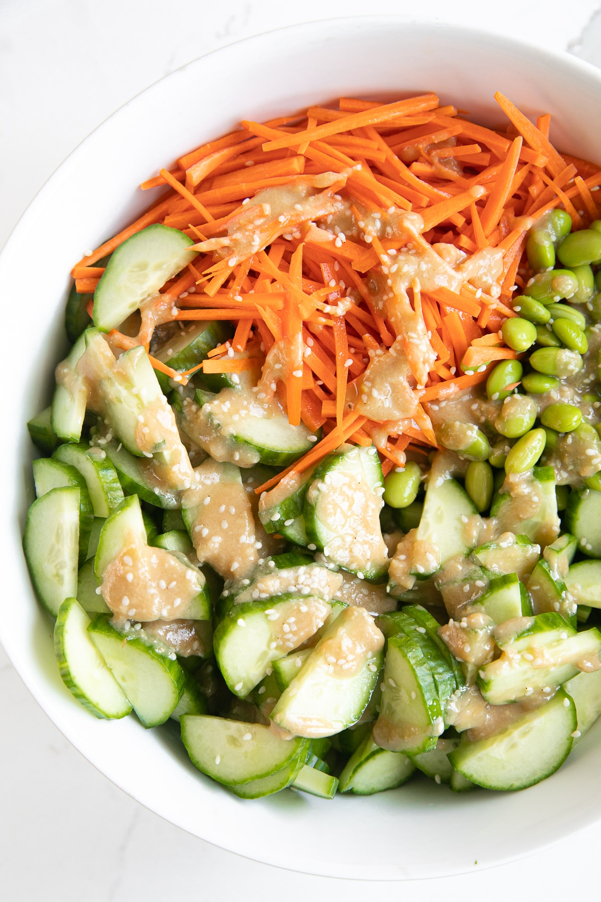 Large white salad bowl filled with julienned carrots, sliced cucumbers, and edamame and drizzled with homemade miso dressing.