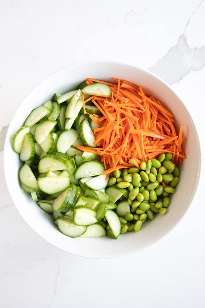 White salad bowl filled with julienned carrots, edamame, and sliced cucumbers.
