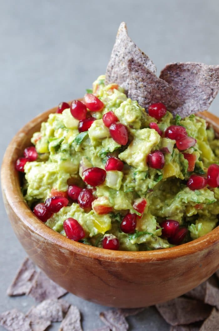 Mango Guacamole covered in pomegranates in wooden bowl