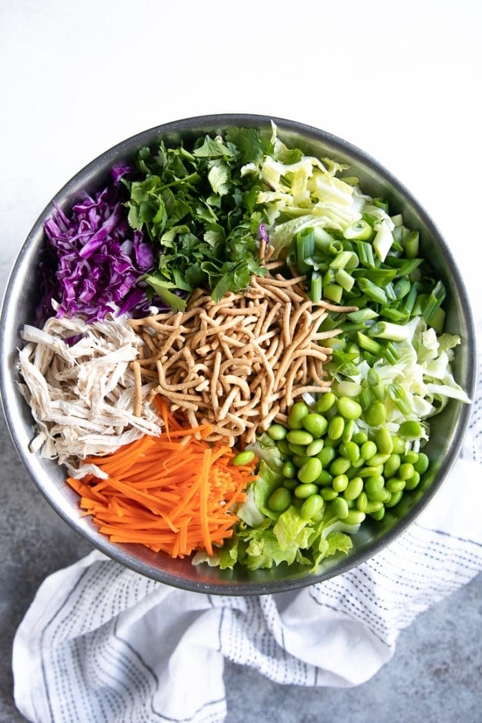 Large mixing bowl filled with chow mein noodles, cilantro, cabbage, lettuce, edamame, carrots, shredded chicken, and green onion.