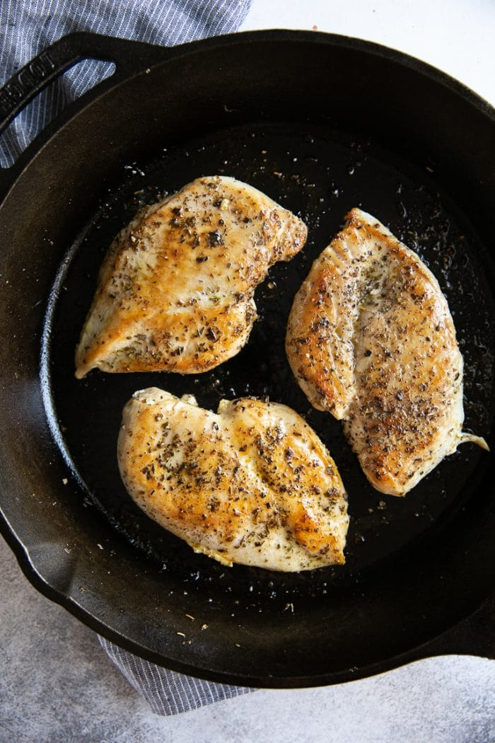 Three fully cooked chicken breasts in a large cast iron skillet.