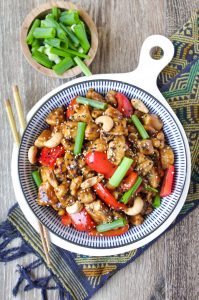 Cashew Chicken in a large blue and white serving bowl garnished with sesame seeds and green onions.