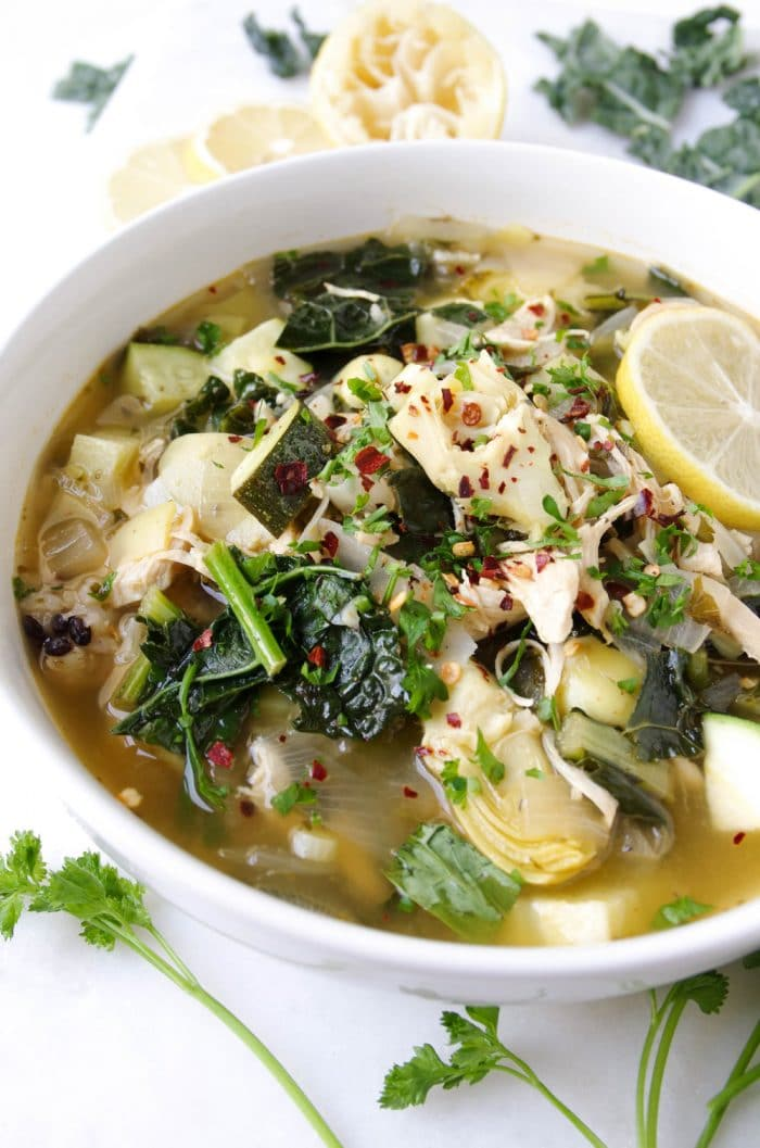 White serving bowl filled with chicken soup made with wild rice, artichoke hearts, zucchini and kale.