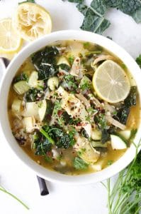 Soup bowl filled with chicken, kale, and rice soup garnished with fresh lemon wedges.