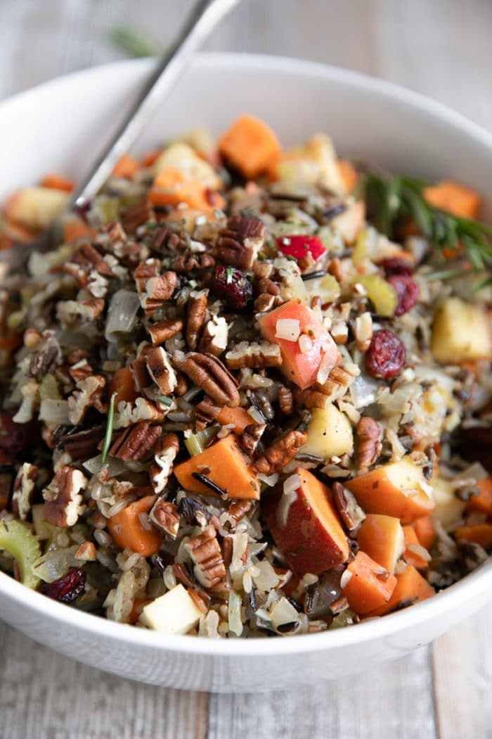 White serving bowl filled with wild rice pilaf and sweet potatoes, apples, pecans, apples, dried cranberries, and herbs.
