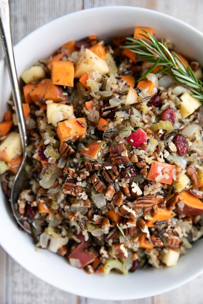 Large white serving bowl filled with cooked wild rice blend mixed with sweet potatoes, dried cranberries, apples, and fresh herbs.