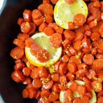 Carrots in a skillet with lemons oranges and maple syrup
