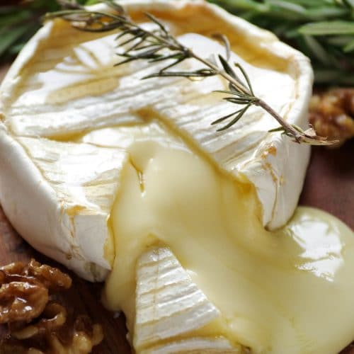 Block of baked brie on a small wood serving board sliced open with gooey cheese oozing out.