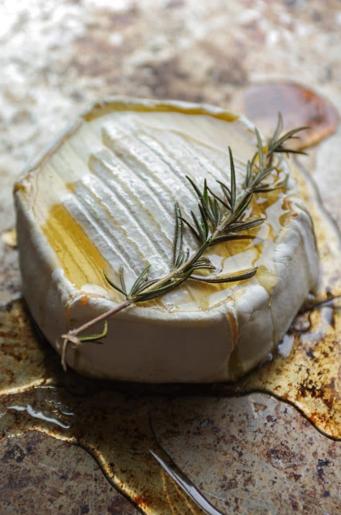 SIde view of baked brie covered in warm dripping honey and charred sprig of fresh rosemary.
