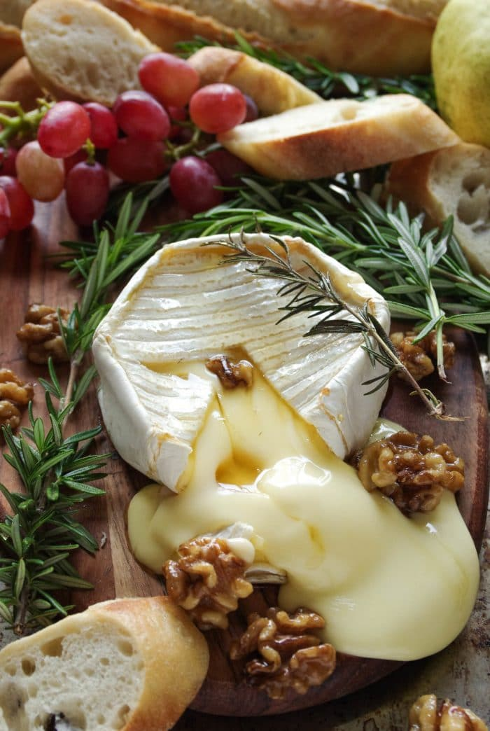 Gooey baked brie with maple candied walnuts on a small wood serving board with grapes and sliced bread.