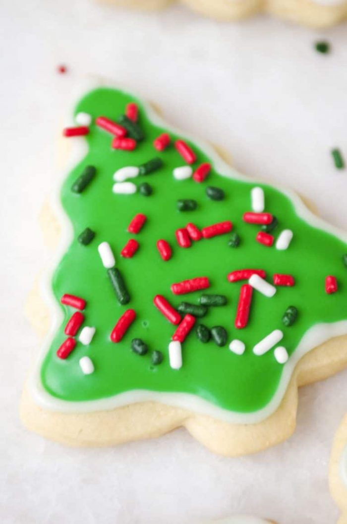 One Christmas tree sugar cookie decorated with icing and red, green and white sprinkles.
