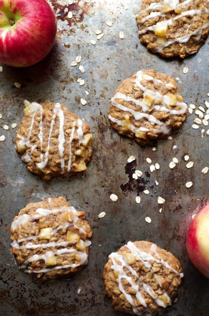 Oatmeal cookies filled with fried apples and drizzled with a sweet sugar glaze on a large baking sheet.
