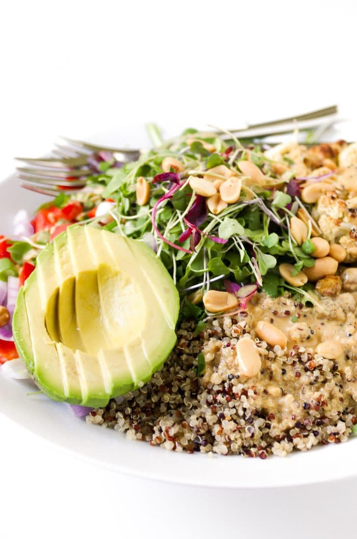 Quinoa buddha bowl filled with roasted chickpeas and roasted cauliflower with avocado, microgreens, chopped bell pepper, onions, and Peanut Butter Coconut Milk Dressing.