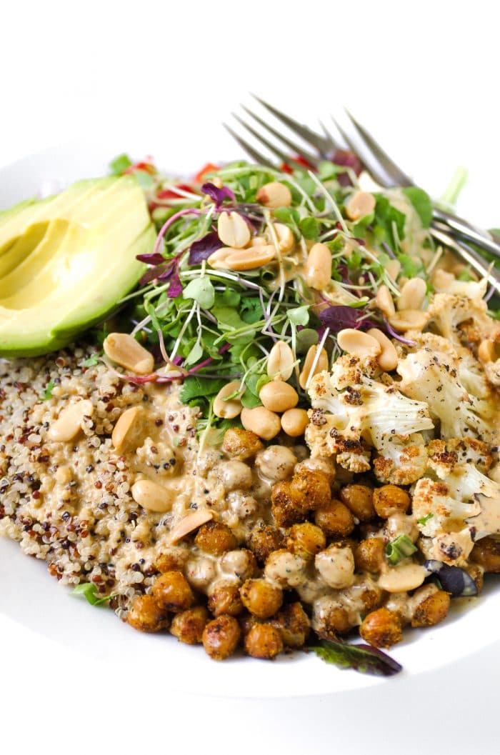 Large white bowl filled with cooked quinoa, roasted cauliflower, chickpeas, microgreens, avocado, and Peanut Butter Coconut Milk Dressing.
