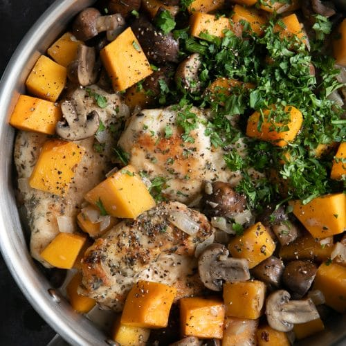 Large pan filled with cooked chicken breasts, butternut squash, mushrooms, and garnished with fresh parsley