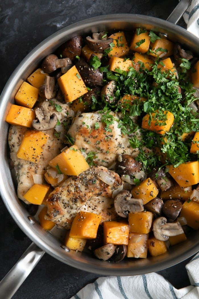 Pot filled with chicken, butternut squash, and mushrooms in a light cream sauce.