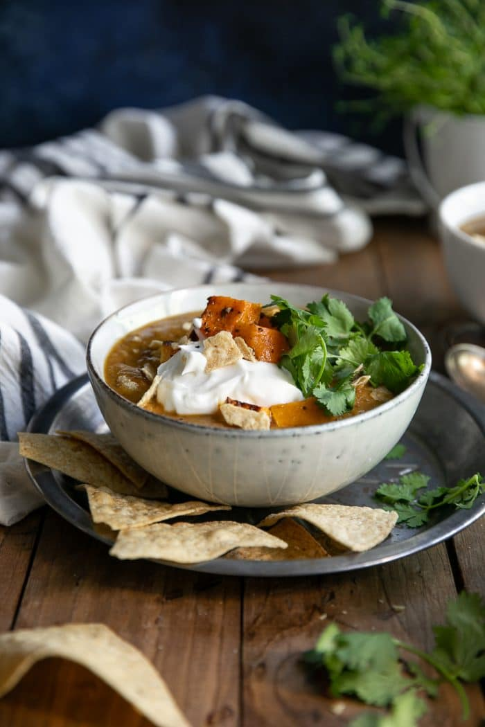 bowl of Vegetarian Butternut Squash Black Bean Soup garnished with roasted butternut squash, cilantro, tortilla chips, and sour cream