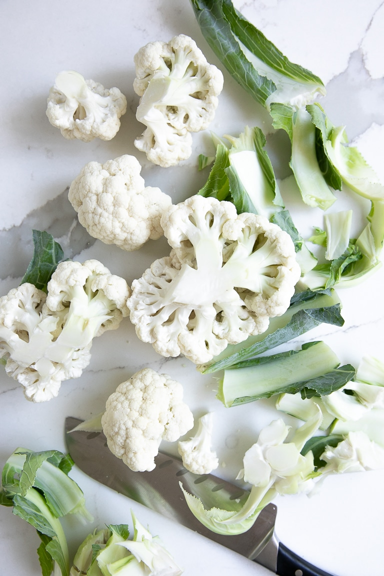 Chopping a large cauliflower into smaller florets.