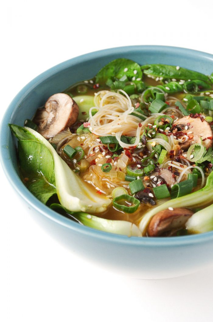 Blue bowl filled with rice noodles, baby bok choy, mushrooms, and healthy vegetarian broth.
