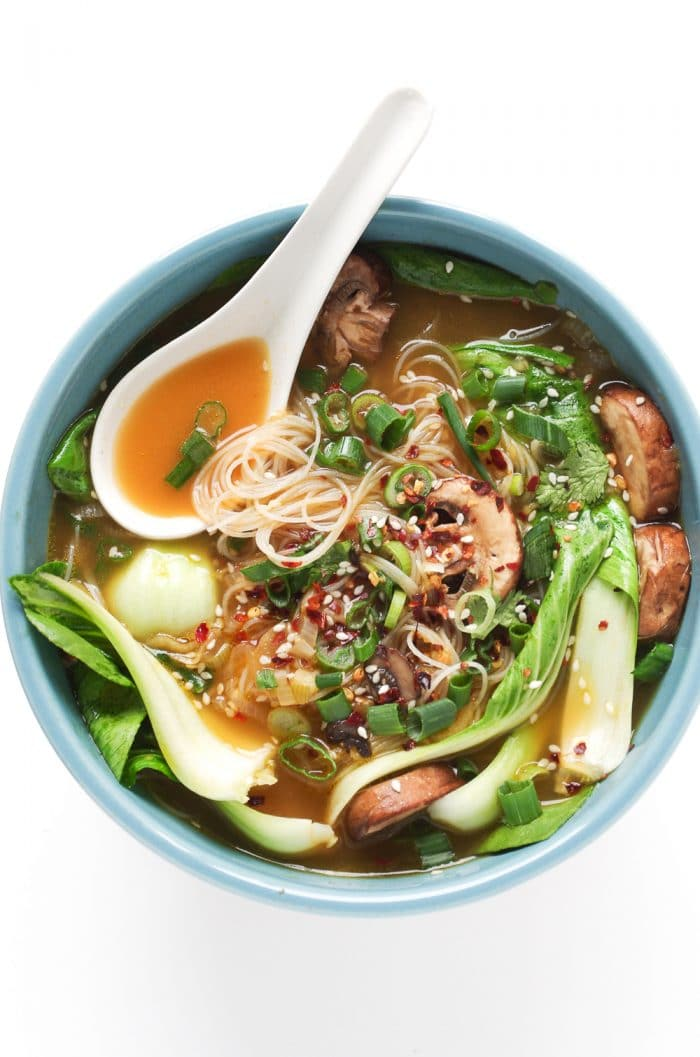 Bowl filled with broth flavored with star anise and soy sauce, noodles, bok choy, mushrooms, and onions