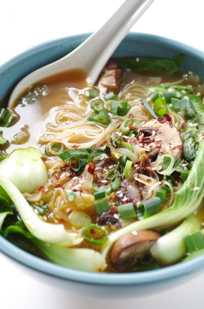 Healthy bowl of ginger garlic noodle soup filled with baby bok choy and mushrooms