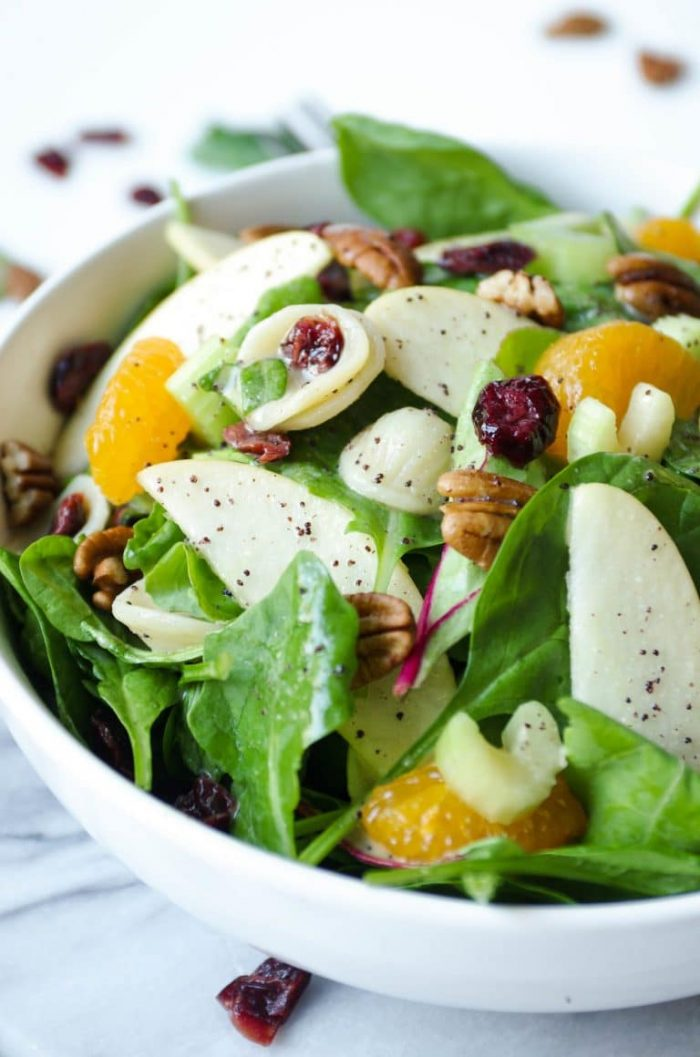 Close up image of a large serving bowl filled with a light spinach pasta salad filled with mixed greens, cooked pasta, mandarin orange slices, dried cranberries, whole pecans, and poppyseed dressing.