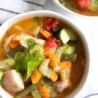 Large white soup bowl filled with a brothy vegetable soup.