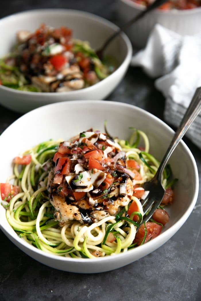 White bowls filled with cooked zucchini noodles and topped with Bruschetta Chicken.