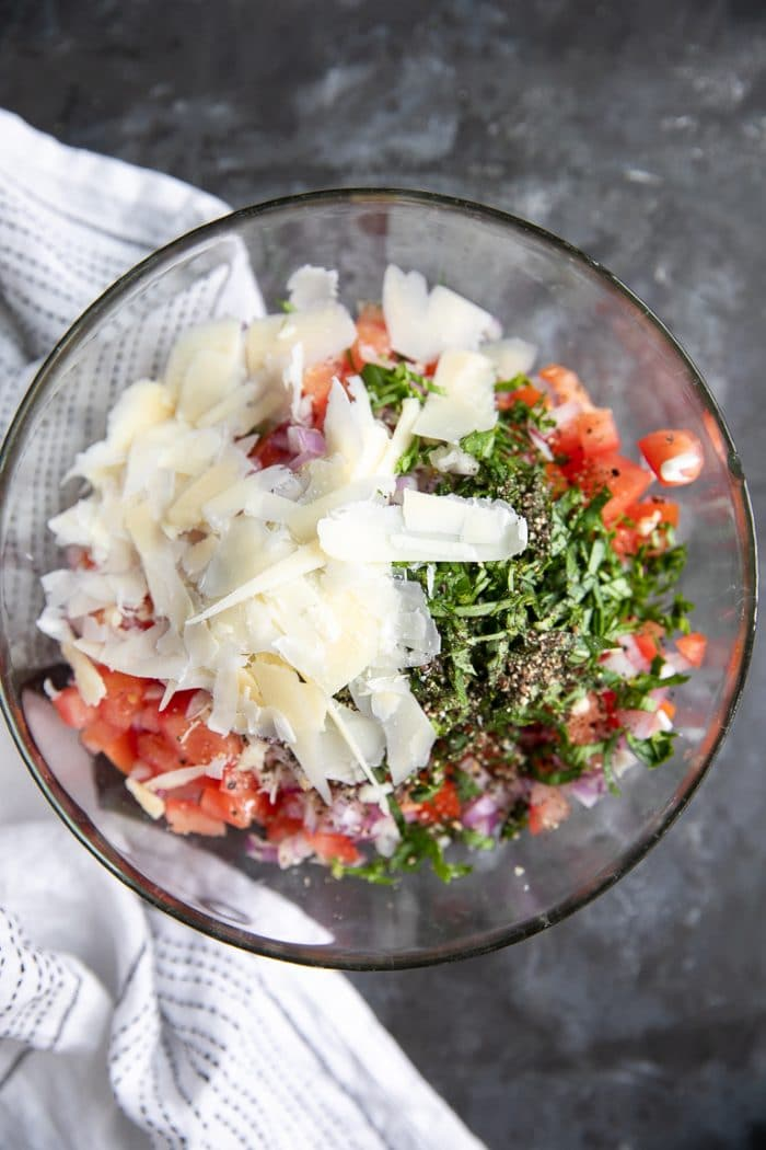 A glass bowl filled with chopped tomatoes, onions, salt, pepper, garlic, fresh basic, and shaved parmesan cheese.