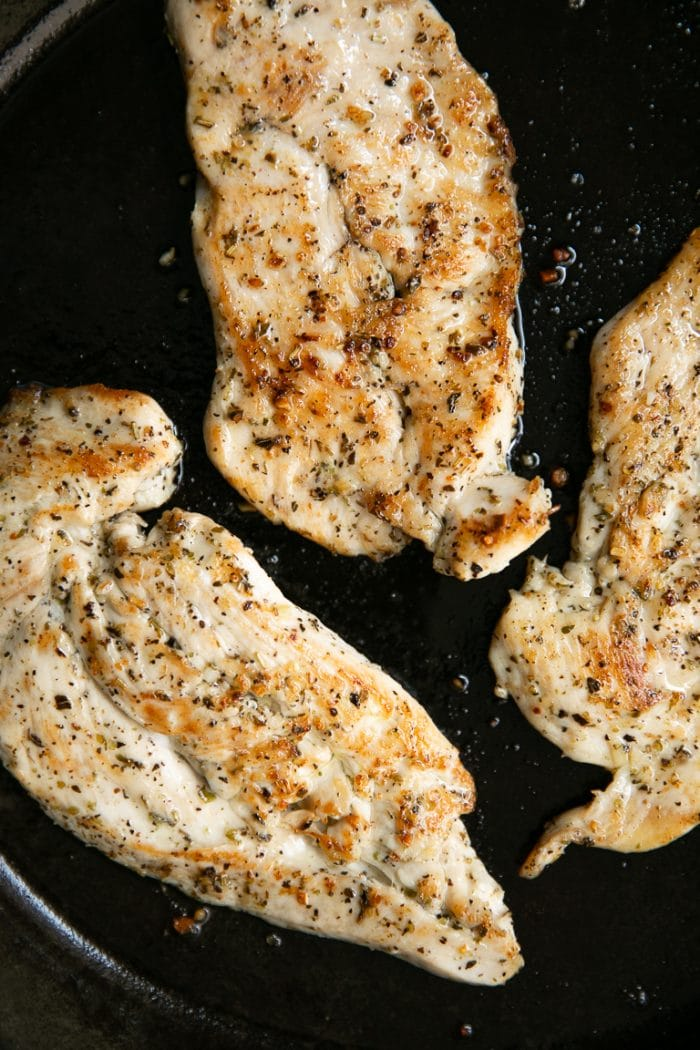 Three thinly sliced cooked chicken breasts in a cast iron skillet.