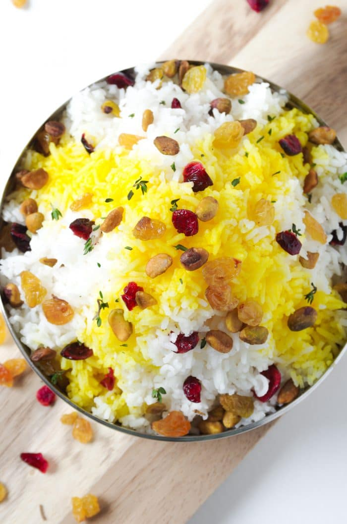 Cooked jasmine rice with saffron, pistachios, dried cranberries, and fresh thyme.