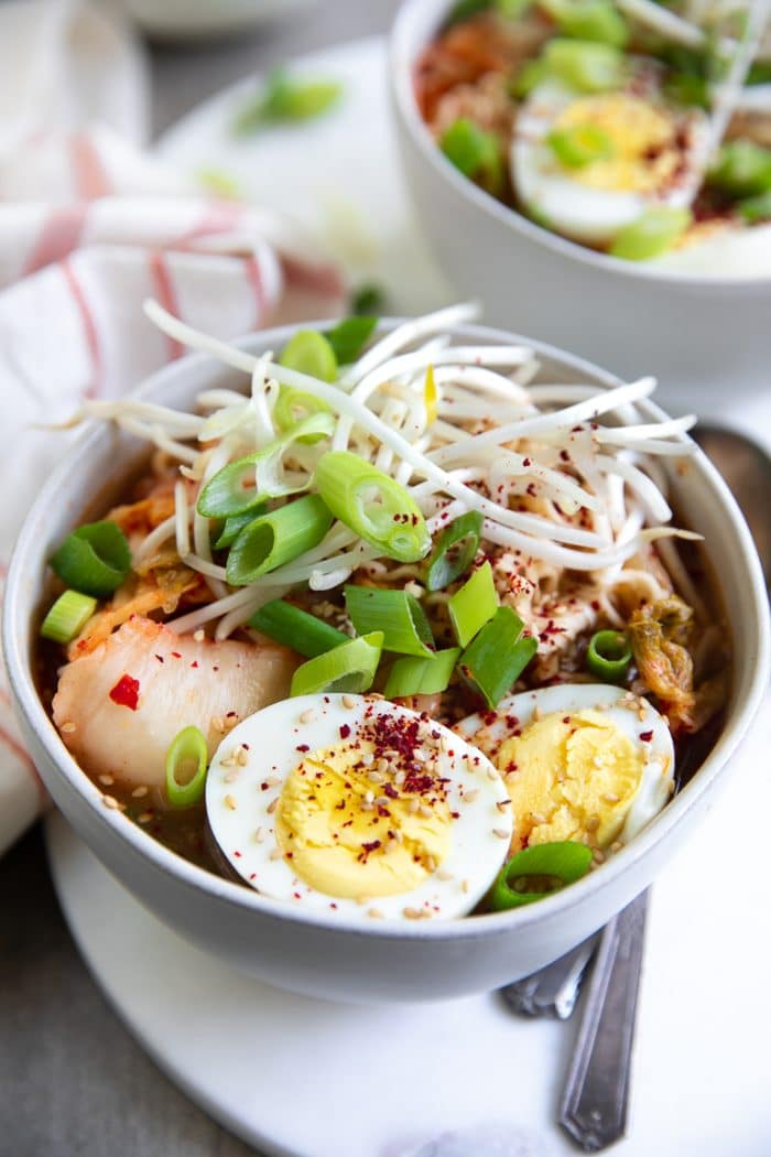 Close-up image of Kimchi Ramen Soup with kimchi, egg, green onion, bung bean sprouts.