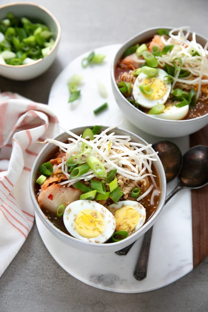 Easy Kimchi Ramen filled with sprouts, hard boiled egg, and green onion