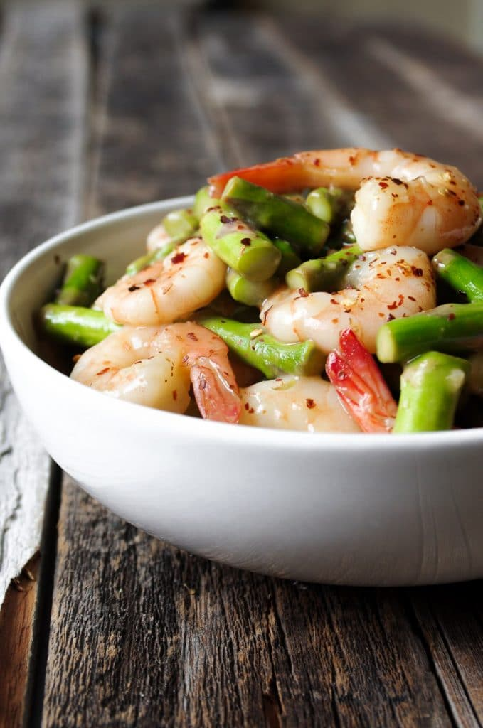 White bowl filled with shrimp and asparagus stir fry dinner