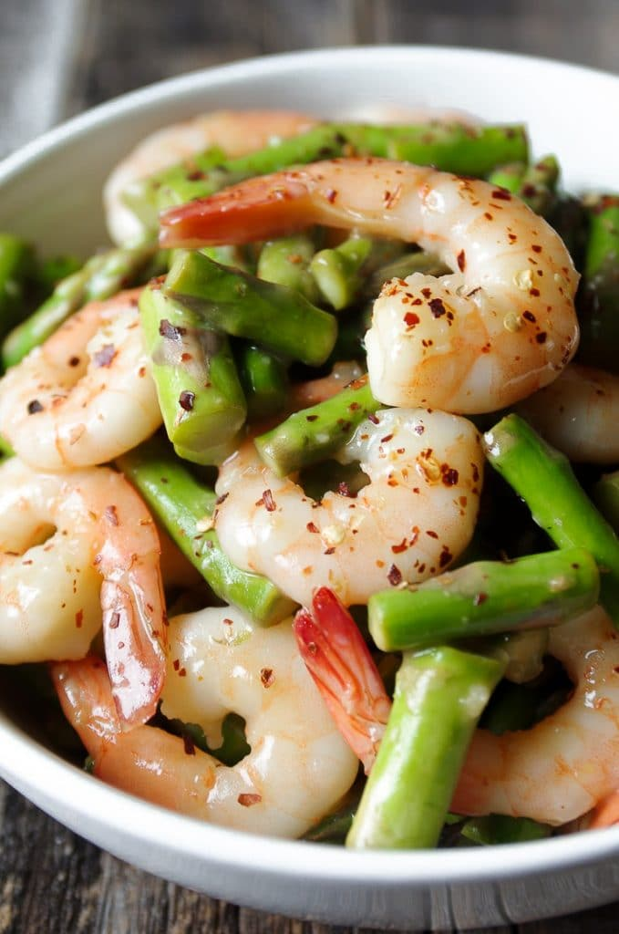 Close up image of cooked shrimp and asparagus in a lemony stir-fry sauce
