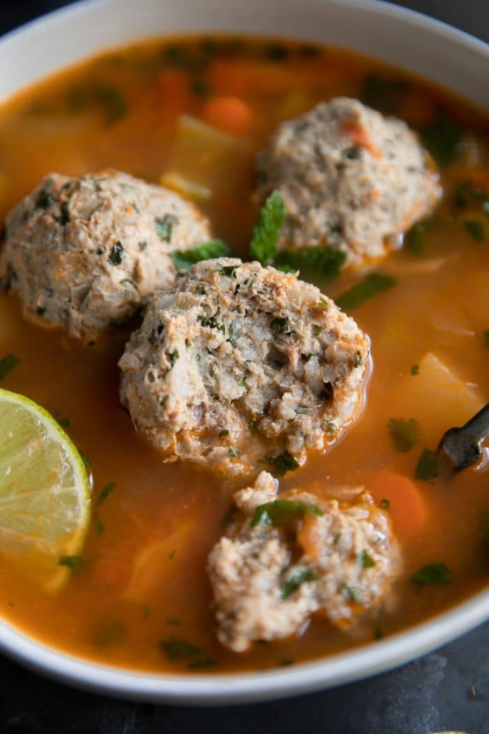 Bowl of albondigas soup garnished with mint leaves, cilantro, and lime.