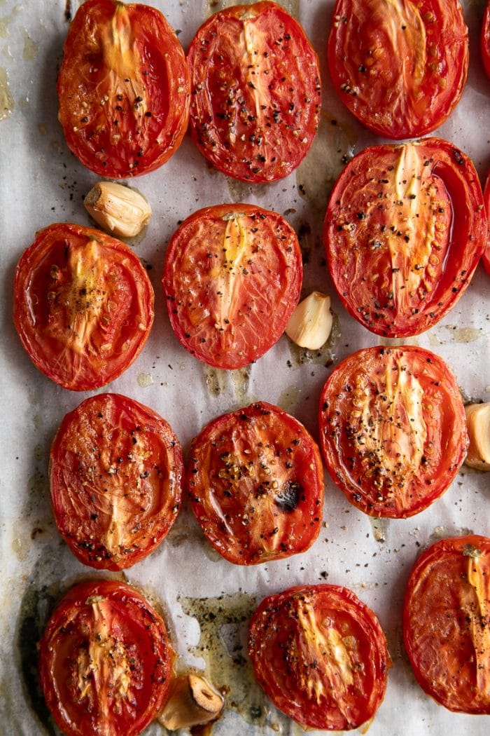 Oven Roasted tomatoes and garlic on a sheet pan.